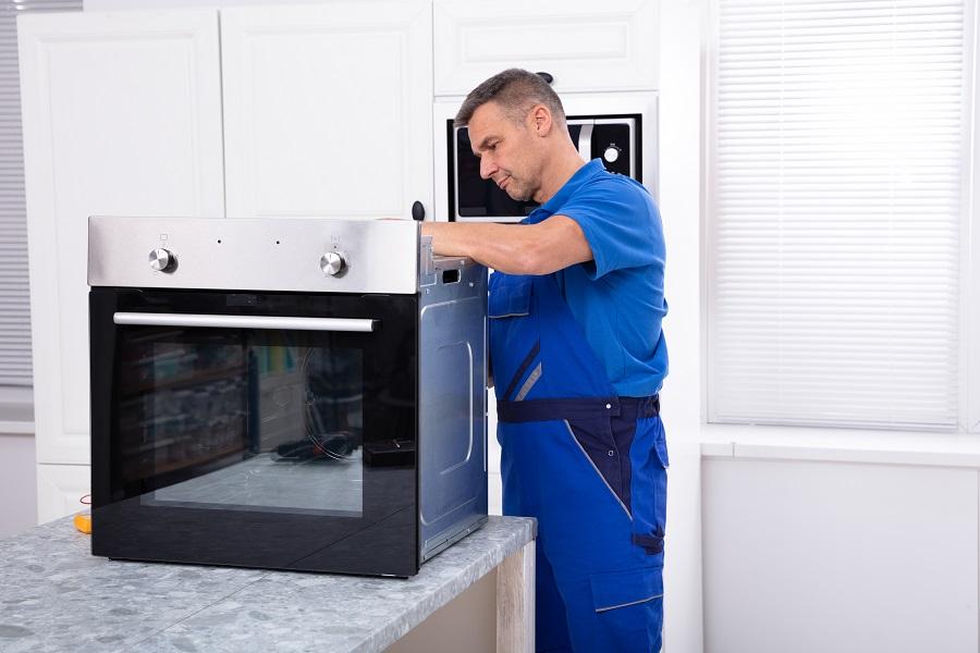 Oven technician repairing oven on kitchen worktop Perth